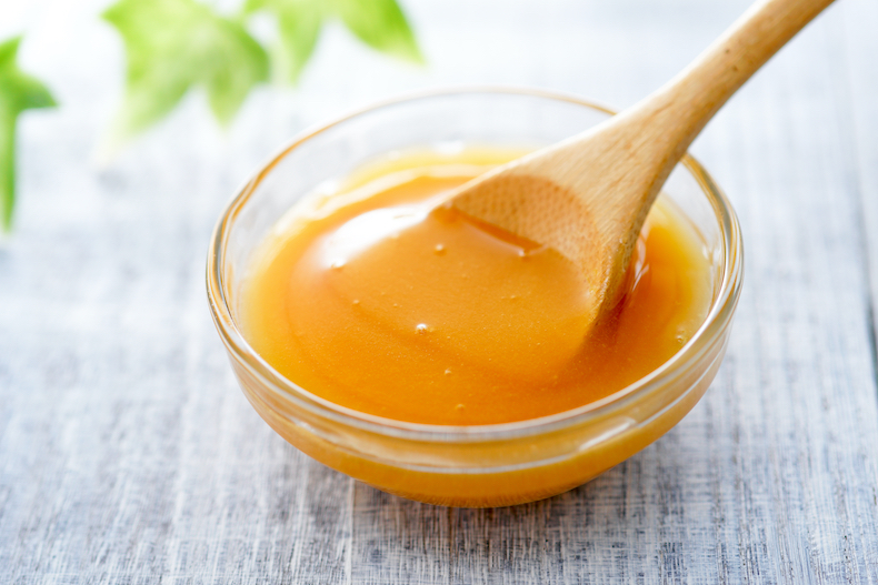Manuka honey and wooden spoon