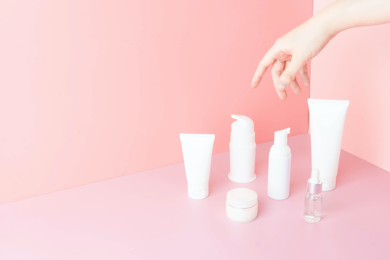 Cosmetic products in the pink wall paper