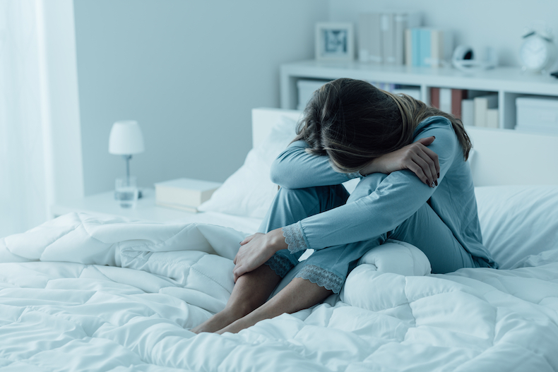 A depressed woman on the bed